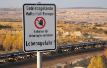 A sign at a German lignite surface mine warns visitors to stay away from the edge of an overlook. A giant earth-moving machine sits on the far horizon.