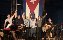 """The """"Cuban Five,"""" a group of five intelligence officers recently returned to Cuba in an exchange with the United States, celebrate on stage with musical artist Silvio Rodriguez."""