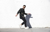 Man in sunglasses in dance pose in front of white, brick wall