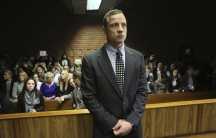 Oscar Pistorius enters the dock before court proceedings at the Pretoria Magistrates court in 2013.