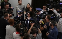 Israel's Ambassador to Poland, Anna Azari, is surrounded by photographers and security officials.