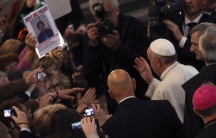 """Pope Francis waves to faithful as he arrives to lead an audience with the family members of victims of the mafia at the San Gregorio VII church in Rome. A woman shows a picture of her son with the words, """"Where is my son?"""""""