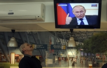 A local resident watches a TV broadcast of Russian President Vladimir Putin's news conference, in Kiev.