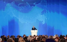Russian President Vladimir Putin addresses the Federal Assembly in Moscow, standing at a podium in front of a large blue map of Russia.