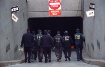 Officers walk into a building through a parking ramp