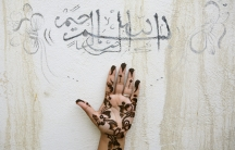 "An Iranian woman holds up her hand, painted with henna, under a religious sentence as she prepares for a wedding ceremony in the city of Qeshm on Qeshm Island at the Persian Gulf, November 1, 2006. The sentence reads, ""In the name of Allah, the Beneficent"