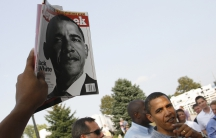 hand holds up magazine with Barack Obama on cover, with Obama nearby