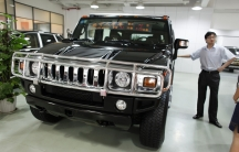 A salesman stands next to a Hummer for sale at an auto trading center in Shanghai on June 3, 2009.