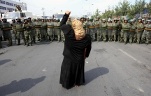 A local woman on a crutch shouts at Chinese paramilitary police as a crowd of angry locals confront security forces on a street in the city of Urumqi in China's Xinjiang Autonomous Region in 2009.