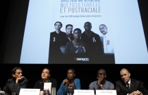 Rokhaya Diallo speaking on a panel below a screen that says in French, 'call for a multicultural and postracial republic'