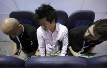 "Melvyn Koh, at center, tries out Italian company Aviointeriors' aircraft ""standing seat"" which has 23 inches of legroom instead of the current economy class average of 30 inches."