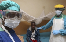 Sierra Leonean nurse Veronica Koroma (left) and doctor Donald Samuel Grant (right) stand by a patient in the Lassa fever ward at Kenema Government Hospital in February, 2011