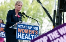 A blond woman is speaking into a microphone at a podium with a sign on the front that says