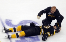 A trainer kneels over the Boston Bruins' Nathan Horton after Horton was hit by the Vancouver Canucks' Aaron Rome in Boston, Massachusetts, June 6, 2011.