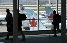 Passengers walk past Air Canada planes on the runway at Pearson International Airport in Toronto April 13, 2012.
