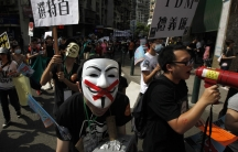 """Pro-democracy demonstrators wearing Anonymous masks hold placards during a protest march demanding universal suffrage for Macau on May 1, 2012. The placard reads """"Vote for Chief Executive."""""""