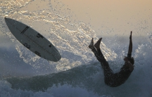 A surfer falls from his board while riding after sunset in Cardiff, California.