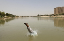 A Bagdad resident plunges into the Tigris river, sandals and all.