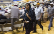 Woman walks past crowd in gymnasium
