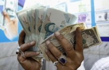 A woman holds up Iranian rials and dollars in a market