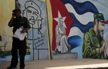 Man makes cell phone call in front of Cuban independence mural in Havana in 2013.
