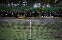 Big plastic bags containing radiated soil, leaves and debris are dumped at a tennis court at a sports park near the Fukushima Daiichi nuclear power plant