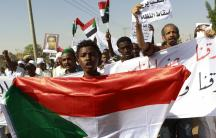 A man holds a Sudanese flag as he chants slogans against the government's deadly crackdown on people protesting against subsidy cuts late last month, during a demonstration after Friday prayers in north Khartoum