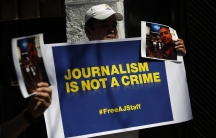 Protesters hold a sign and photographs of detained Al-Jazeera journalists Peter Greste, an Australian, Mohamed Fahmy, a Canadian-Egyptian national, and Baher Mohamed, an Egyptian. The three who were jailed in Cairo on December 29, 2013. Greste was release