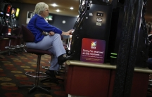 A visitor to the Shell Club, a sports and social venue, plays a slot machine near the Shell Oil refinery in Geelong, Australia.