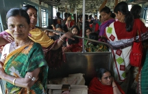 Female passengers travel in the crowded ladies' compartment of a local train in Kolkata, India.