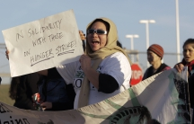 """Woman holds up sign that readers """"In solidarity with those on hunger strike"""""""