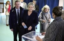 France's far-right National Front political party leader Marine Le Pen, center, prepares to cast her ballot at a polling station during the first round of the French mayoral elections in Henin Beaumont, Northern France, March 23, 2014.