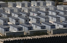 "African immigrants walk among rows of prefabricated container houses, which have replaced scores of tents, at the open centre for immigrants formerly known as ""Tent City"" in Hal Far, outside Valletta March 27, 2014. In 2013"