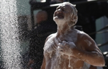 A man takes a shower as policemen patrol during an operation in Rio de Janeiro's Mare slums complex on March 30, 2014.