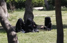 Veiled women sit as they chat in a garden in the ISIS-controlled province of Raqqa in northern Syria.