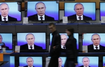 Visitors walk past TV sets during Russian President Vladimir Putin's live broadcast nationwide phone-in at the DNS electronic shop in Russia's Siberian city of Krasnoyarsk.