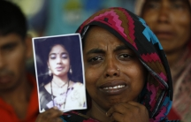 A woman holds a picture of her relative, a garment worker who went missing in the Rana Plaza collapse,  on the first year anniversary of the accident.