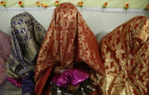 Brides sit together during a mass wedding ceremony in Peshawar, Pakistan, April 25, 2014.