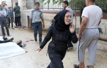 A woman runs past bodies after, according to activists, two barrel bombs were dropped by forces loyal to Syria's President Bashar Al-Assad in Aleppo, Friday.