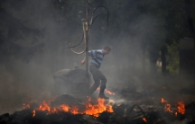 A man jumps over a burning barricade outside the city hall in Mariupol, Friday.