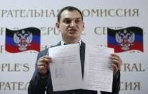 Roman Lyagin, head of the electoral commission in Donetsk, holds up the results of the referendum on the status of the province, during a news conference Monday. Pro-Russian separatists say they received overwhelming support.