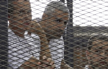 Al Jazeera journalists (L-R) Peter Greste, Mohammed Fahmy and Baher Mohamed stand behind bars at a court in Cairo last summer.