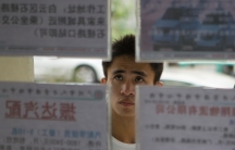 A job seeker looks at recruitment advertisements at a labor market in Guangdong province, where most people speak Cantonese.