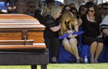 Andrea Soldo is consoled by family members after receiving a flag during the funeral services for her husband, Las Vegas police officer Igor Soldo, in Las Vegas, Nevada, on June 12, 2014.