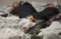 Detainees sleep in a holding cell at a US Customs and Border Protection processing facility, in Brownsville, Texas on June 18, 2014.