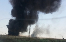 Smoke rises from a oil refinery in Baiji, north of Baghdad, in this picture taken through the windscreen of a car, June 19, 2014. Iraqi government forces battled Sunni rebels for control of the country's biggest refinery on Thursday as Prime Minister Nuri