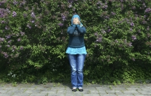 A Syrian refugee covers her face to hide her identity as she poses for a photograph at an asylum camp outside Stockholm, June 8, 2014.