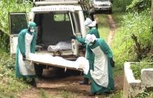 Health workers carry the body of an ebola virus victim in Kenema, Sierra Leone.