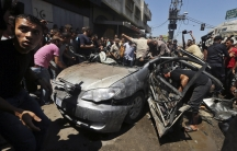 Palestinians in Gaza City gather around the remains of a car which police said was targeted in an Israeli air strike on Tuesday.