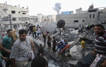 Smoke rises from buildings following what witnesses said was an Israeli air strike, as Palestinians search for victims under the rubble of a house which police said was destroyed in another Israeli air strike in Rafah in the southern Gaza Strip, on July 1